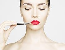 拿唇笔化妆的美女特写摄影图片