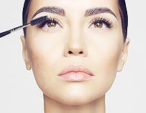 仰头刷睫毛膏的美女近景摄影图片