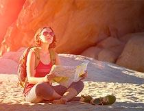 坐在沙滩上看地图的美女摄影图片