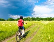 乡间田野上骑自行车的男孩摄影图片