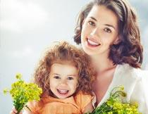 拿着油菜花的温馨母女摄影图片