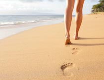 海滩上行走的人物局部特写摄影图片