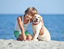 跪在沙滩上拥抱小狗的男孩摄影图片