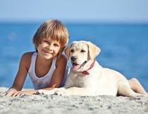 趴在沙滩上的快乐男孩与狗摄影图片