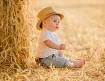 坐草地上戴草帽的宝宝摄影图片