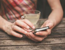 喝茶玩手机的美女局部特写摄影图片