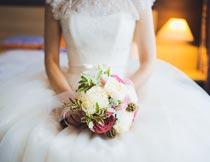 坐床上拿着捧花的新娘摄影图片