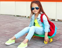 坐在滑板上的时尚墨镜女孩摄影图片