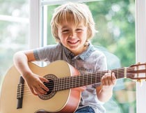坐窗台上弹吉他的小男孩摄影图片