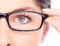 手扶镜框的美女眼睛特写摄影图片