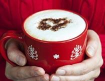 捧在手中的红色咖啡杯摄影图片