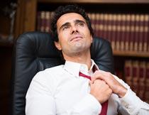 坐办公椅上解领带的商务男士摄影图片