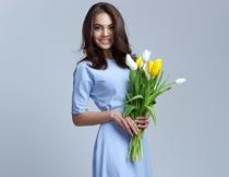 穿蓝色裙子手捧花束的美女摄影图片