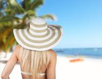 海边戴帽子的性感美女背影摄影图片
