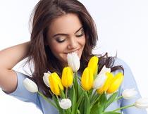 低头笑手拿郁金香的美女摄影图片