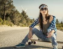 坐在滑板上的潮流女孩摄影图片