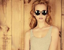 戴墨镜的美女与木板背景摄影图片