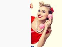 广告牌后打电话的美女模特摄影图片