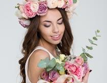 看手中花朵的花环美女写真摄影图片