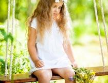低头坐秋千上的漂亮女孩摄影图片