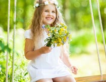 拿着鲜花荡秋千的可爱女孩摄影图片
