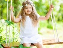 树林里荡秋千的小女孩摄影图片