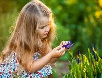 蹲着摘花的可爱女孩写真摄影图片