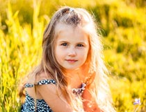坐在草丛上的漂亮女孩特写摄影图片