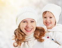微笑着背起孩子的漂亮母亲摄影图片