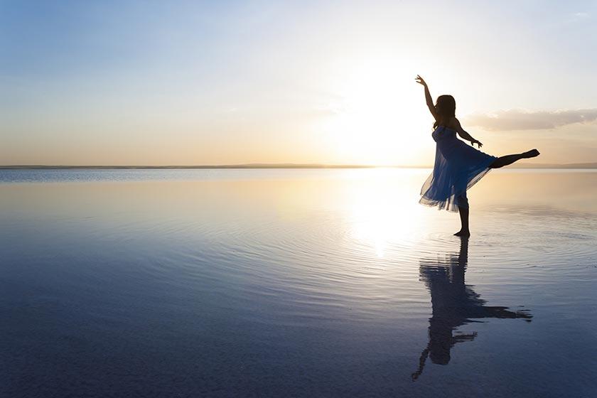 海边单腿站立起舞的美女摄影图片