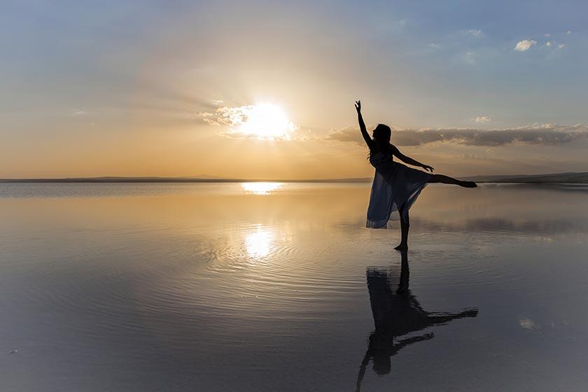 海边舞蹈的美女逆光剪影摄影图片
