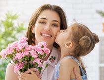捧着花束亲妈妈脸颊的女孩摄影图片