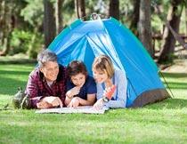 帐篷内看地图的家庭野营摄影图片