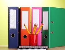 桌上的彩色文件夹与笔筒摄影图片