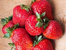 木板上新鲜采摘的草莓特写摄影图片
