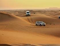 行驶在荒芜沙漠上的越野车摄影图片