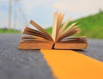 道路上打开的书本特写摄影图片