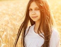 金色麦田里的长发小女孩摄影图片