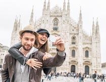 欧式建筑前手机拍照的情侣摄影图片