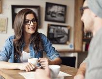 边喝咖啡边聊天的情侣写真摄影图片
