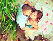 浪漫花瓣下亲吻的婚纱新人摄影图片