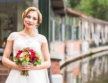 笑着拿红色花束的美丽新娘摄影图片