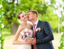 拿捧花开心亲吻的婚纱新人摄影图片