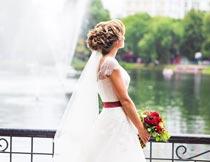 双手拿捧花看湖景的新娘摄影图片