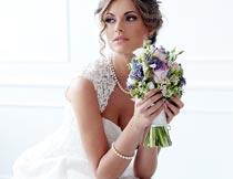 双手捧着花束的婚纱新娘摄影图片