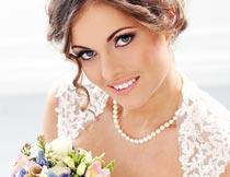微笑着拿着花束的美丽新娘摄影图片