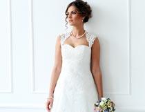 靠在白色门板上的婚纱新娘摄影图片