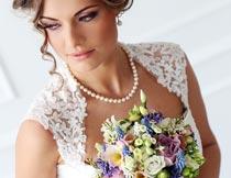双手拿着鲜花的美丽新娘摄影图片