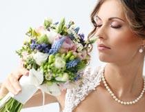 拿着花束闻花香的新娘特写摄影图片