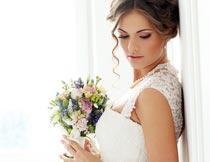 双手捧着花束俯视的新娘摄影图片